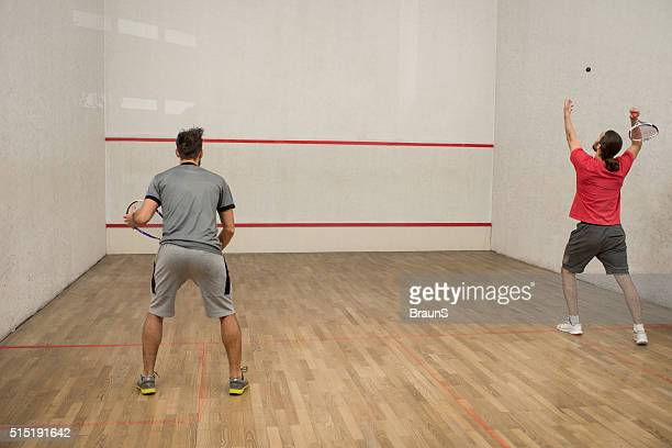 back view of men playing squash on a court. - serving sport stock pictures, royalty-free photos & images