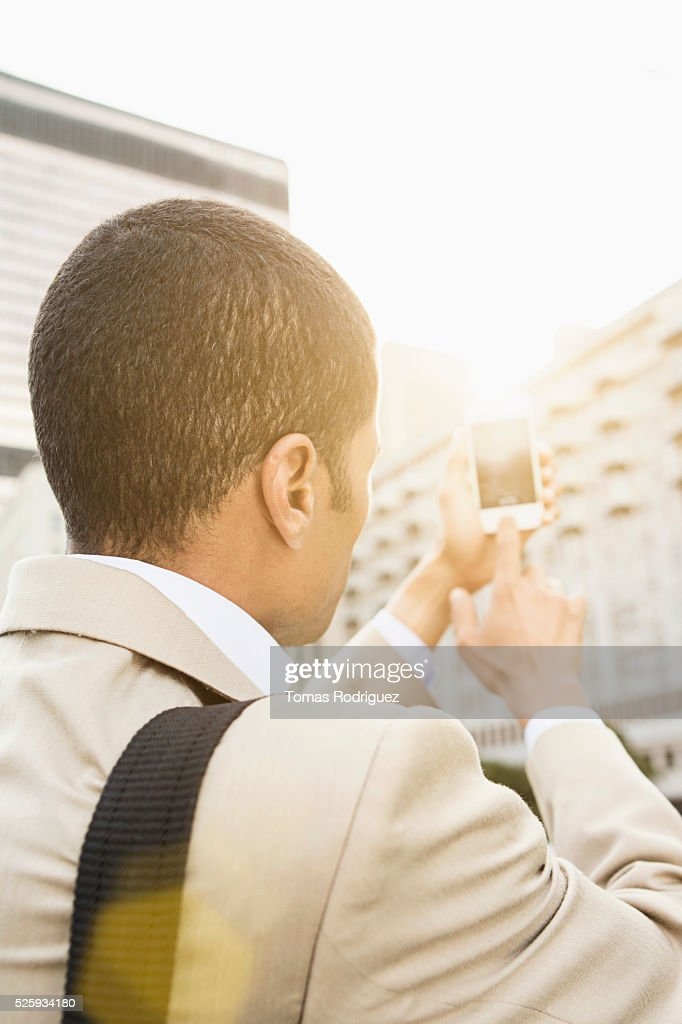 Back view of mid adult man photographing with cell phone : Foto de stock