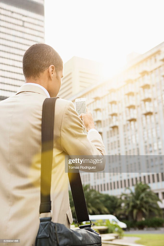 Back view of mid adult man using cell phone : Stock Photo