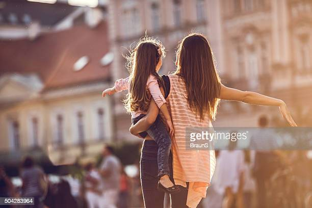 Back view of mother and daughter walking in the city.