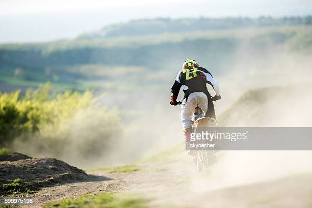 Back view of motocross racer in action on dirt road.