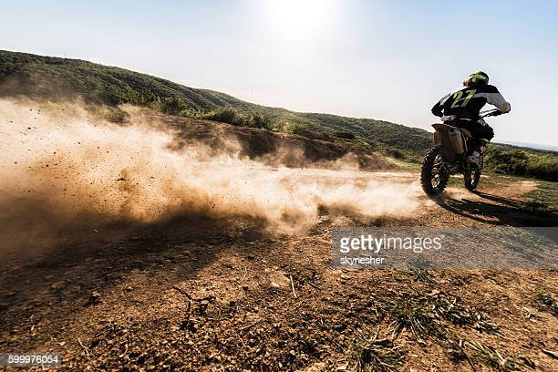 Back view of motocross rider driving fast on dirt track.