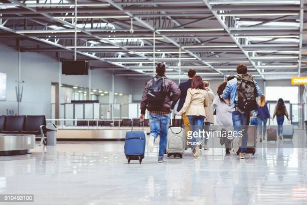 back view of people running with suitcase at airport terminal - izusek stock pictures, royalty-free photos & images