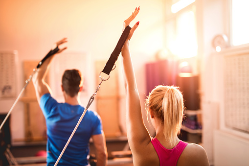 Back view of Pilates reformers exercising in a health club. - gettyimageskorea