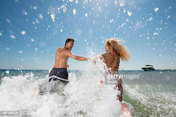 Back view of playful couple running into the sea.