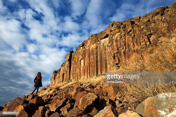 Back view of redhead in black pea coat and leather boots looking up at sheer cliffs
