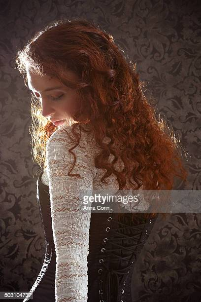 Back view of redhead in lace top and corset