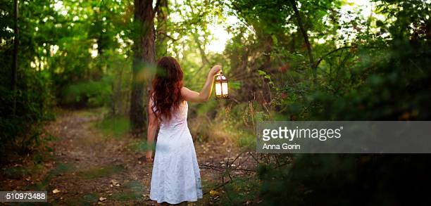 Back view of redhead in white dress holding lit lantern on forest path, dusk