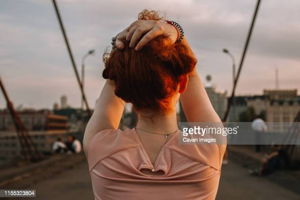 back view of redhead woman holding hair while standing on bridge - look back at early colour photography stock pictures, royalty-free photos & images