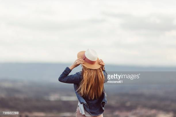 Back view of redheaded woman wearing hat looking at distance