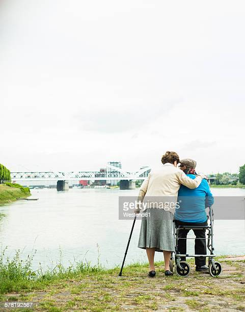 Back view of senior couple standing at waters edge with walking stick and wheeled walker