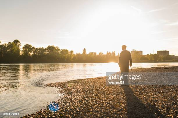 back view of senior man standing at riverside watching sunset - fluss stock-fotos und bilder