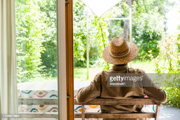 back view of senior man wearing straw hat on terrace enjoying his garden - ein mann allein stock-fotos und bilder