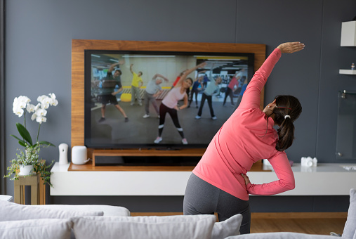 Back view of senior woman following an online stretching class looking at TV screen 1216673974