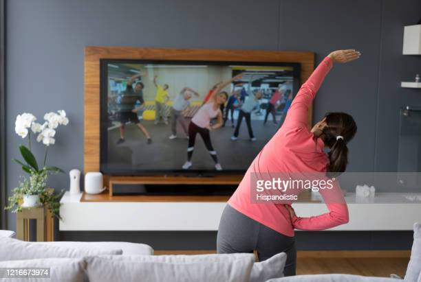 back view of senior woman following an online stretching class looking at tv screen - following moving activity stock pictures, royalty-free photos & images