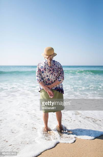 Back view of senior woman standing on the beach