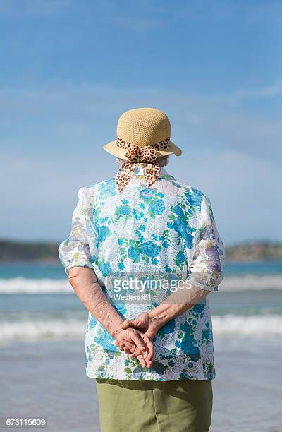 Back view of senior woman wearing straw hat on the beach looking at distance