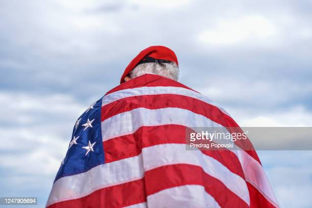 back view of senior world war 2 veteran proudly standing and looking up in the dramatic sky - hero and not superhero stock pictures, royalty-free photos & images