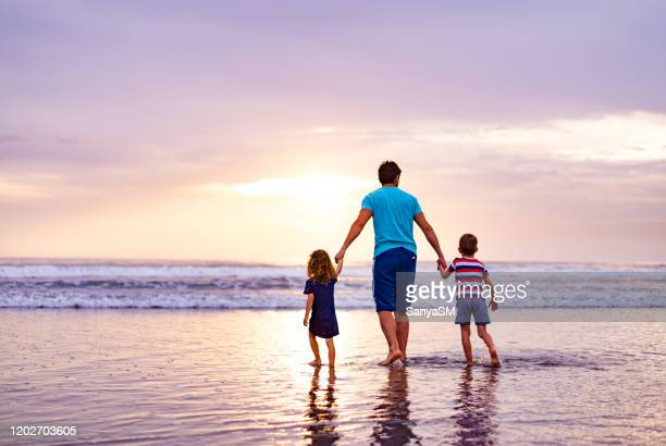 back view of single father and children running on the beach at dusk - single father stock pictures, royalty-free photos & images