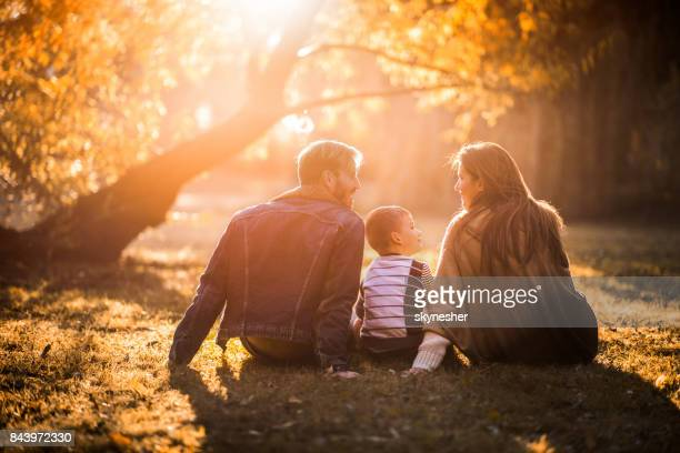 back view of smiling family communicating in autumn day at sunset. - fall back stock photos and pictures