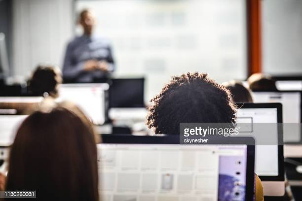 back view of students attending a class at computer lab. - computer lab stock pictures, royalty-free photos & images