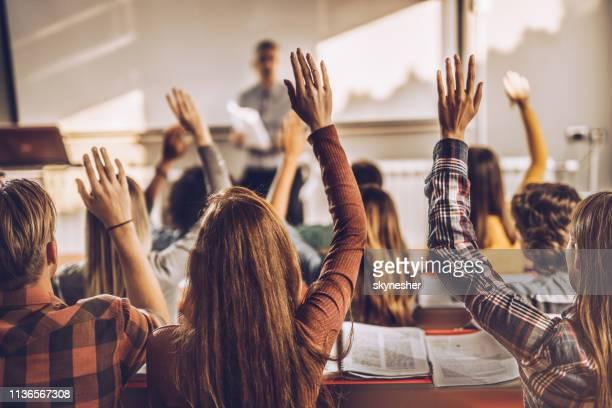 back view van de studenten het verhogen van de handen op een klas in collegezaal. - armen omhoog stockfoto's en -beelden