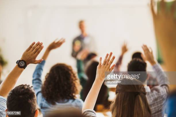 back view of students raising hands on a class. - asking stock pictures, royalty-free photos & images