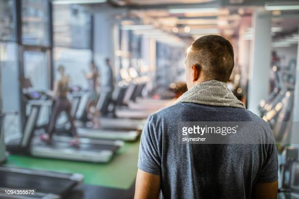 back view of sweaty athlete in a gym. - sweat stock pictures, royalty-free photos & images