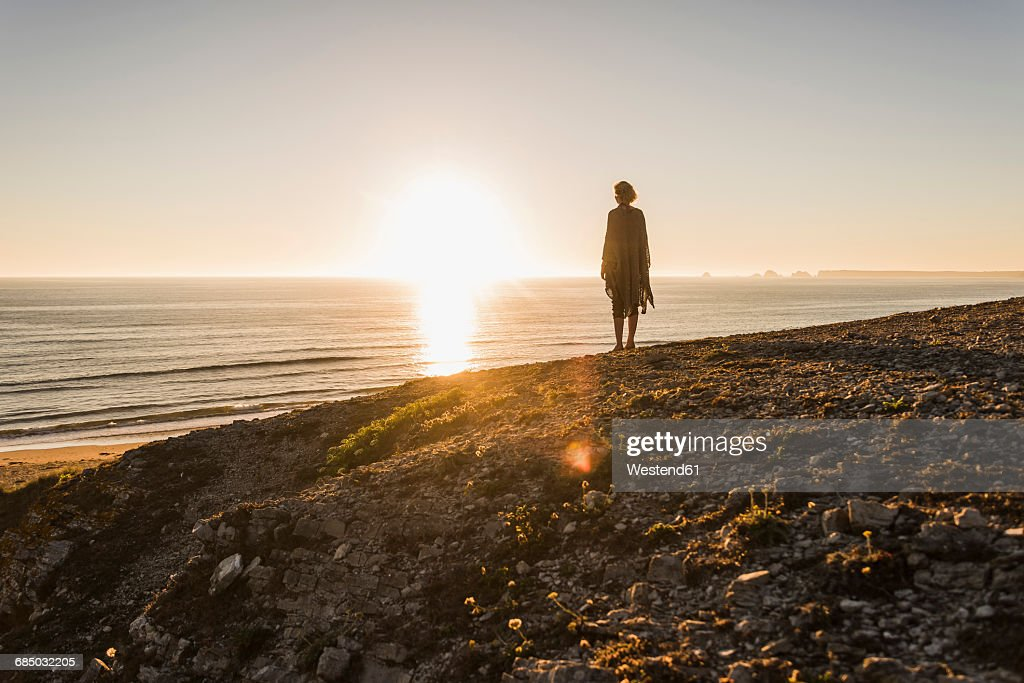 back view of teenage girl standing on hill at sunset looking to the