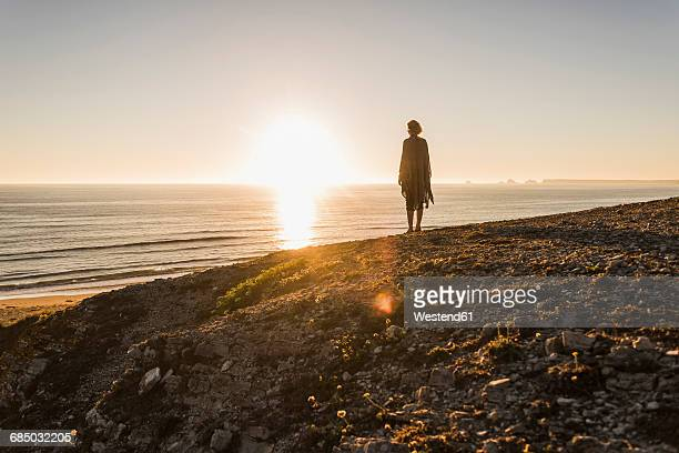 back view of teenage girl standing on hill at sunset looking to the sea - finistere stock photos and pictures