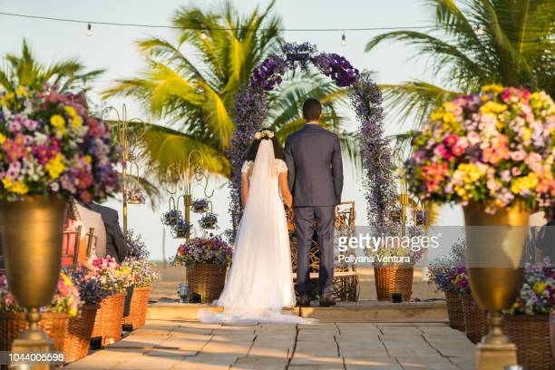 back view of the bride and groom at the altar - cerimonia di nozze foto e immagini stock