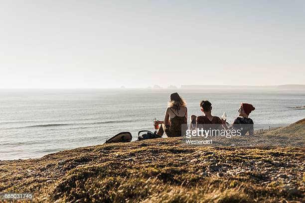 back view of three friends relaxing at seaside - finistere stock photos and pictures