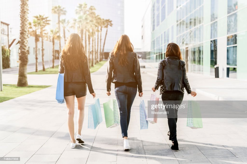 Back view of three friends with shopping bags : Foto de stock