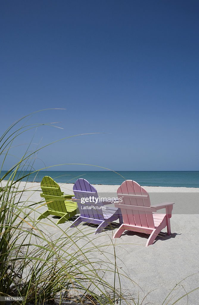 Back view of three pastel colored beach chairs on sand : Stock Photo