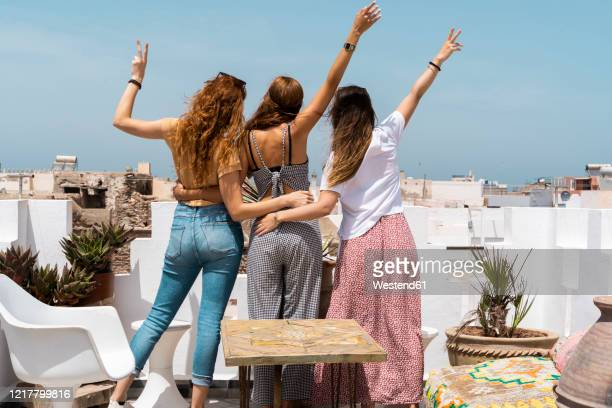 back view of three young women standing on roof terrace showing victory signs, essaouira, morocco - north africa stock pictures, royalty-free photos & images