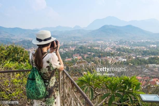 back view of tourist woman looking to beautiful view of luang prabang town from the top of mt.phu si (or mt.phou si) high hill in the centre of the old town of luang prabang in laos. - unesco stock pictures, royalty-free photos & images