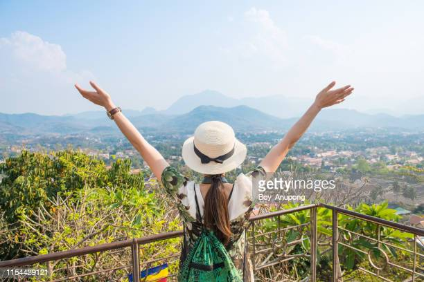 back view of tourist woman raised her hands and looking to beautiful view of luang prabang town from the top of mt.phu si (or mt.phou si) high hill in the centre of the old town of luang prabang in laos. - unesco stock pictures, royalty-free photos & images