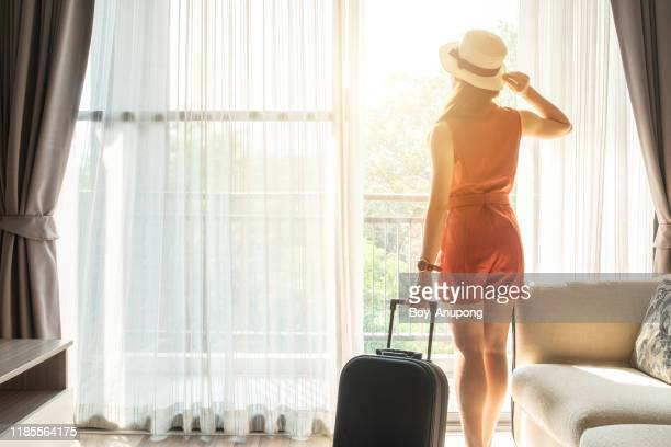 back view of tourist woman standing nearly window, looking to beautiful view with her luggage in hotel living room after check-in. - hóspede - fotografias e filmes do acervo