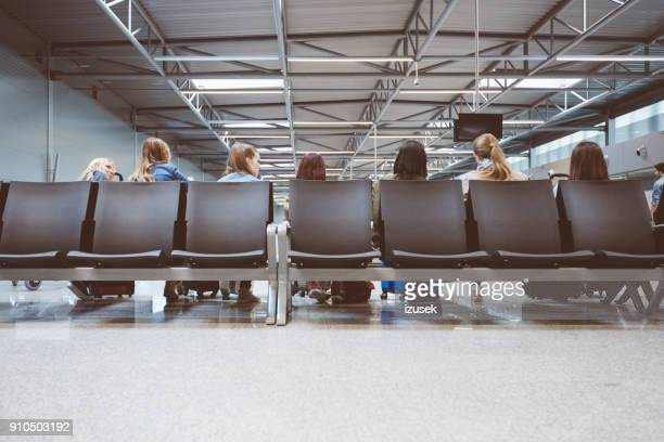 Back view of travelers in international airport waiting for flight