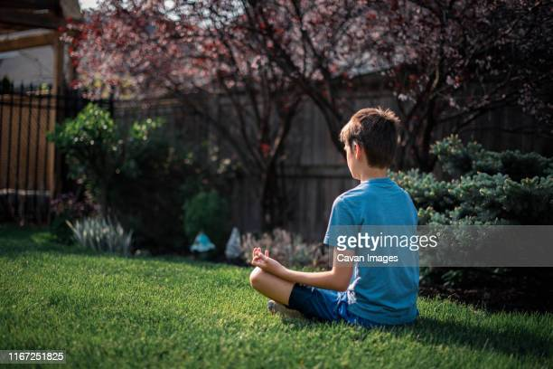 back view of tween boy sitting on the grass in a garden meditating. - children only stock pictures, royalty-free photos & images