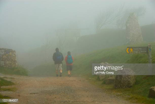 back view of two hikers in mist walking along wales coast path. - lyn holly coorg stock pictures, royalty-free photos & images