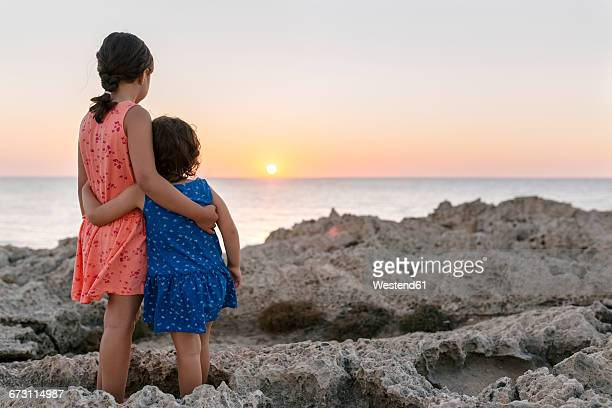 Back view of two little sisters standing arm in arm at rocky coast watching sunset