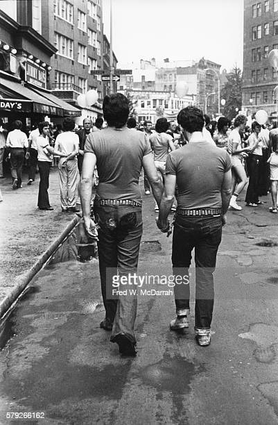 Back view of two paradegoers as they hold hands and walk along a West 4th Street during the Sixth Annual Gay Pride Day March New York New York June...