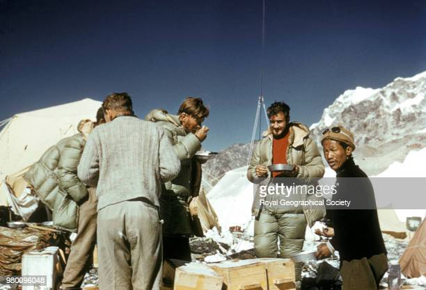 Back view of two team members plus Wylie Noyce and Anu eating porridge at Base Camp Nepal March 1953 Mount Everest Expedition 1953