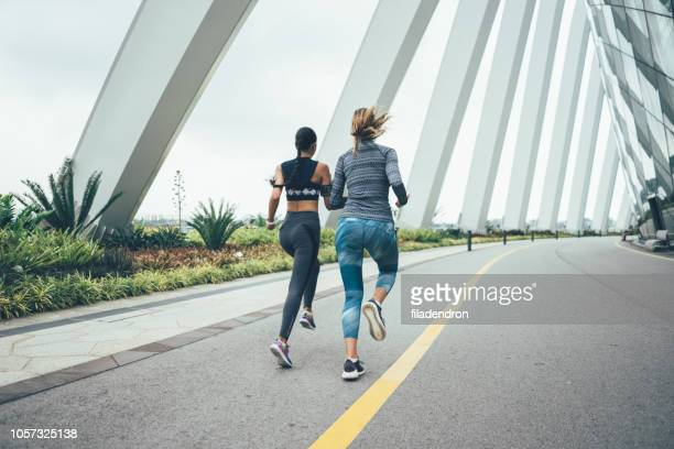 back view of two young sporty women running - sprint stock pictures, royalty-free photos & images