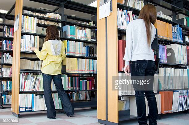 Back View of Two Young Women Standing in Library