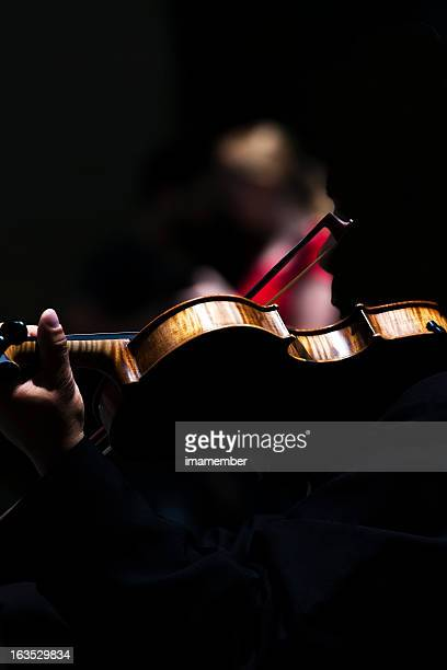 Back view of violinist in dark composition with copy space