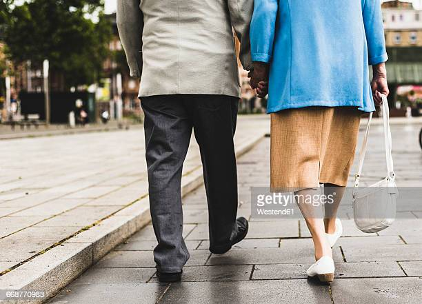 back view of walking senior couple holding hands - human leg stock pictures, royalty-free photos & images