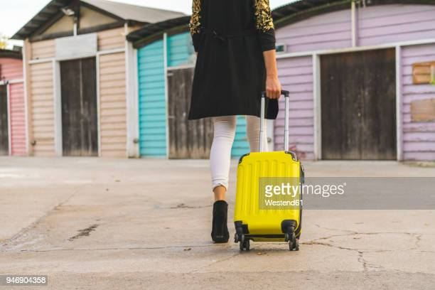 back view of walking woman with yellow trolley bag, partial view - wheeled luggage stock photos and pictures