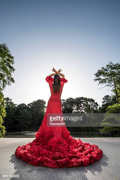 back view of woman dressed in red dancing flamenco on a terrace - flamenco photos et images de collection